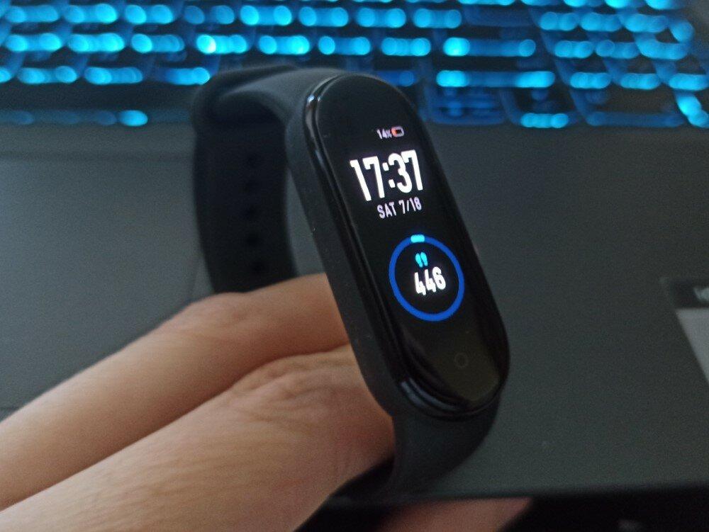 """""""Mi Smart Band 5"""" su įjungtu pagrindiniu ekranu (ciferblatu), matoma platesnė įrenginio forma"""