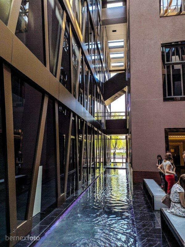 Dirbtinis upelis skiria sanąją ir naująją pastato dalis - iš vienos į kitą galima patekti tilteliu (matomas toliau fone)